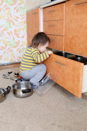curioso bambino da 1 anno guarda in cassetto della cucina