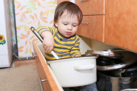 baby plays with pots sitting in drawer on kitchen
