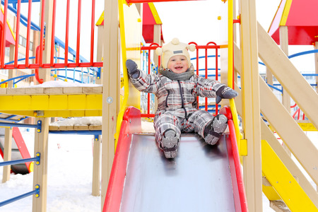 happy baby on slide outdoors in winter photo