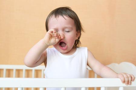 gapende kindje leeftijd van 18 maanden in het wit bed