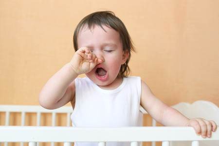 gape: yawning baby age of 18 months in white bed Stock Photo