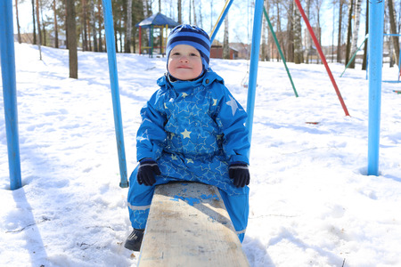 18 months baby sitting on old seesaw outdoors in winter photo