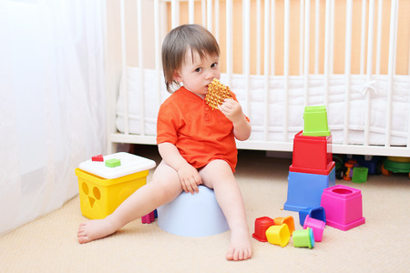 lovely baby boy sitting on potty and eating biscuit