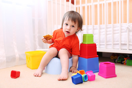 lovely baby boy with toys and waffle sitting on potty Stock Photo