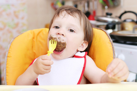 eats: baby age of 20 months eating meat