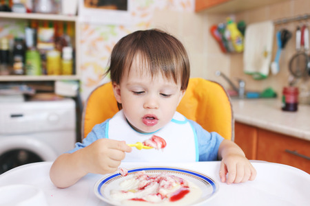 lovely 20 months baby eating semolina porridge Stock Photo