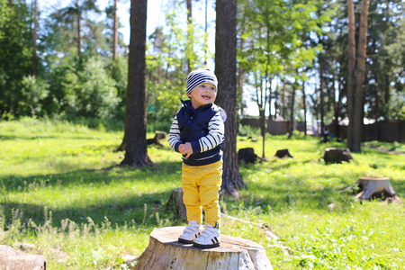 happy baby age of 21 months standing on stub in forest