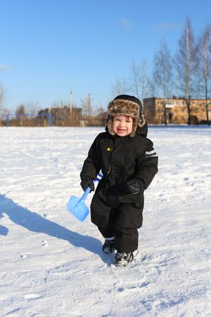 toddler walking: lovely 2 years toddler walking with shovel in winter outdoors