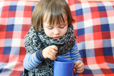 2 years ill toddler in warm woolen scarf and cup of tea