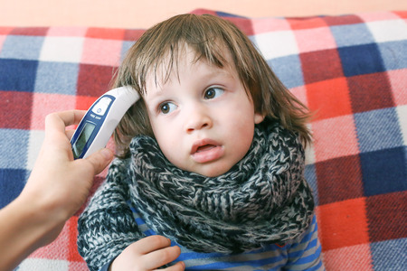 Mother takes temperature for her child with infrared thermometer Stock Photo