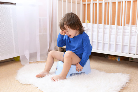 Piangere due anni bambino seduto sul vasino