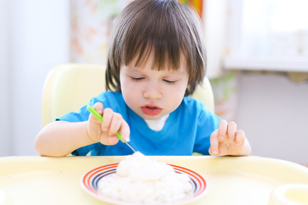lovely 2 years toddler boy eating quark with sour cream