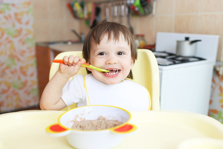 happy baby age of 22 months eats oatmeal Stock Photo