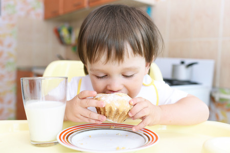 lovely baby eating cupcake and drinking milk