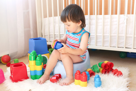 lovely baby boy (22 months) plays toys sitting on potty