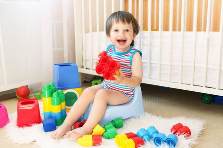 lovely baby boy plays toys sitting on potty