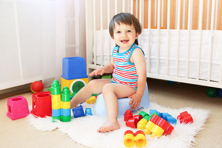 lovely baby with toys sitting on potty