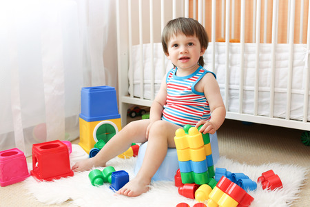 baby with toys sitting on potty Stock Photo
