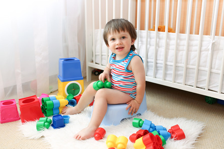 piddle: baby with toys sitting on potty Stock Photo