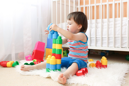 lovely baby boy age of 22 months playing toys at home