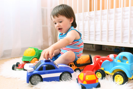 lovely baby boy playing cars Stock Photo