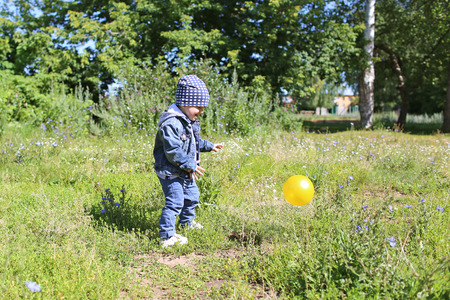 happy baby age of 22 months playing ball outdoors Stock Photo
