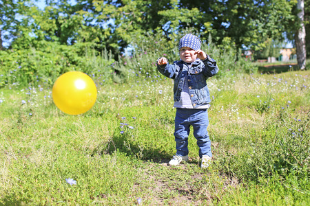 happy baby playing ball outdoors