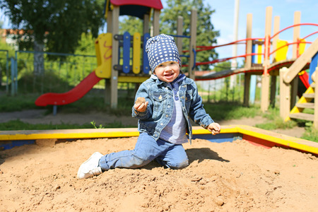 happy little boy (22 months) playing with sand on playground
