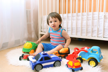 lovely baby boy playing cars at home
