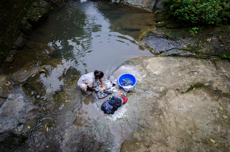 waterscapes: A women washing cloths in a natural wild river goes in Mawlynnong Village, Meghalaya. Stock Photo