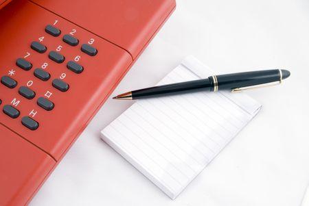 teléfono rojo con lápiz y noteblock