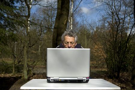 retired man is trying to learn working with laptop photo