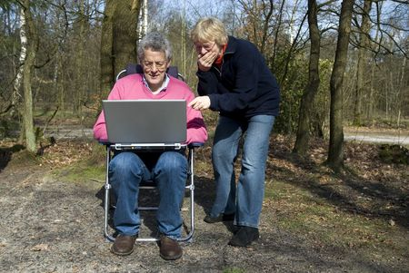 grandparents do have fun together with laptop photo