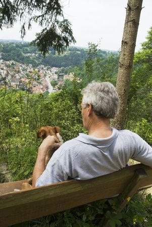 man and dog are above on a mountain and enjoy the viewpoint photo
