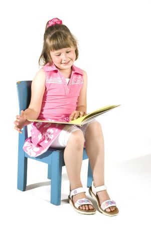 cute little girl is reading a book photo