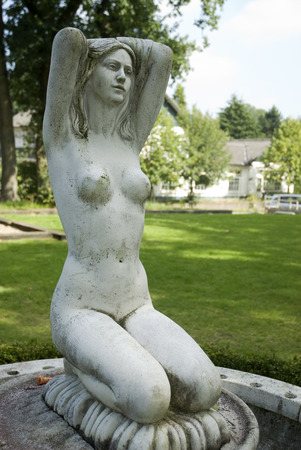 naked statue: naked woman as a fountain in the garden Stock Photo