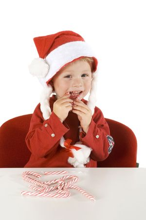 child is eating christmas candy canes photo