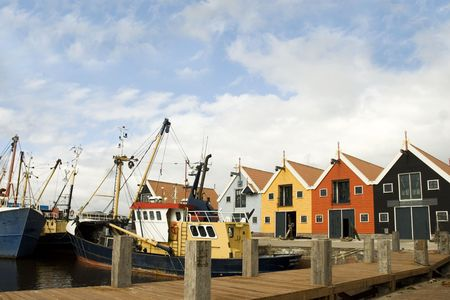 fishingboat: fishing-boat in front of a colored harbor Stock Photo