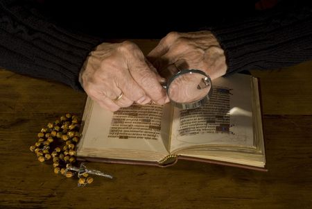 old person is reading and praying with bible and rosary photo