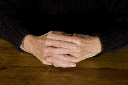 old hands resting at the wooden table photo
