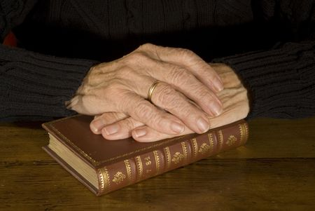 old hands with weddingring resting at closed antique bible photo