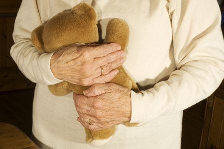 Old demented person is playing with bear Stock Photo - 2338866