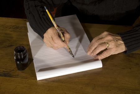 old woman is writing with pencil and ink photo