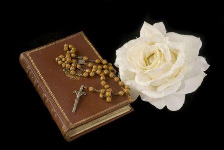 rosary and bible with white rose on black photo