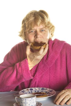 senior woman is eating biscuits while having breakfast photo
