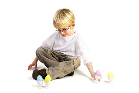 a little blond boy is playing with easter eggs Stock Photo - 2475723