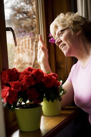 saying: elderly woman is waving and happy with visit Stock Photo
