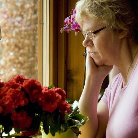 lonely elderly woman is sad sitting by the window Stock Photo - 2713369