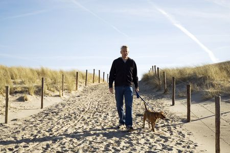 elderly man is walking his dog at the beach Stock Photo - 2713393