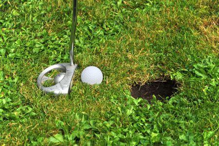 golfball close near the hole photo